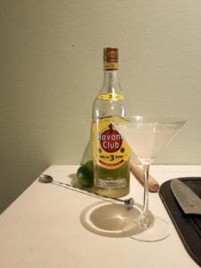 Ett cocktailglas med drinken daiquiri. Bakom ligger en sked, lime och en muddlare. Det står även en flaska rom bakom.