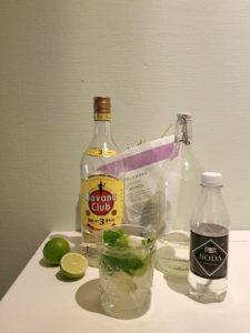 Ett glas med mojito. Bakom står flaskor med sodavatten, sockerlag, och rom, samt en kruka mynta. Det ligger även lime bakom.